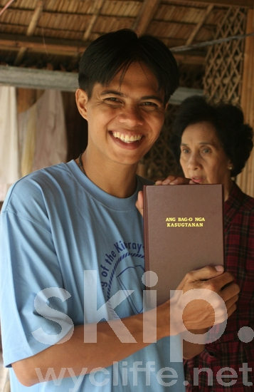 Philippines;smiling;translator;holding new Kinaray-a Bible;village