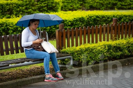 Central America;Costa Rica;San Jose;park;rain;sitting;street photography;umbrella;woman