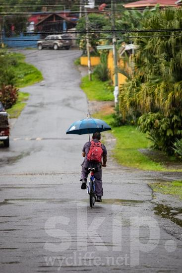 Central America;Costa Rica;San Jose;backpack;bicycle;man;rain;street photography;umbrella