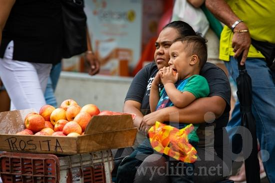 Central America;Costa Rica;San Jose;apples;boy;ear buds;mother;street photography;woman