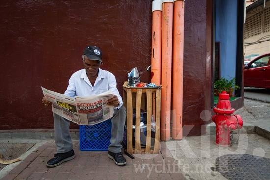 Central America;Panama City;man;newspaper;read;sidewalk;sitting;street photography