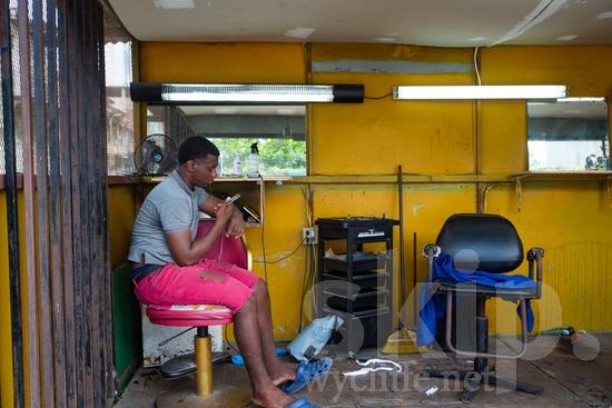 Central America;Panama City;barber;chair;man;phone;sitting;street photography