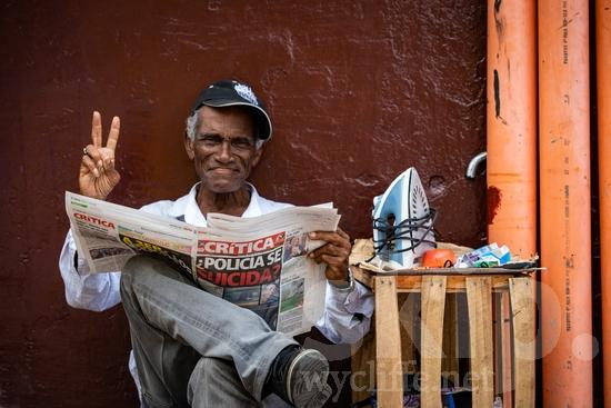 Central America;Panama City;hat;man;newspaper;read;sitting;smile;street photography
